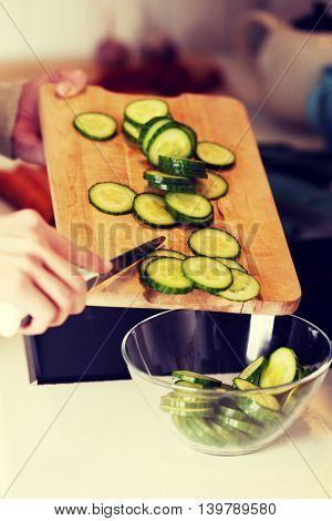 Caucasian attractive young woman is cutting cucumber.