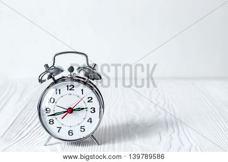alarm clock on an empty locker on white background