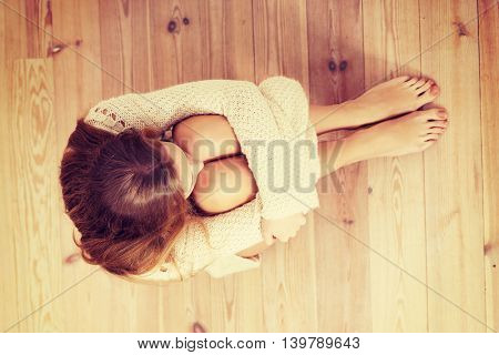 Beautiful caucasian woman is sitting on the floor.