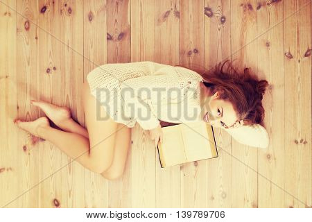 Happy caucasian woman lying on the floor and reading a book.