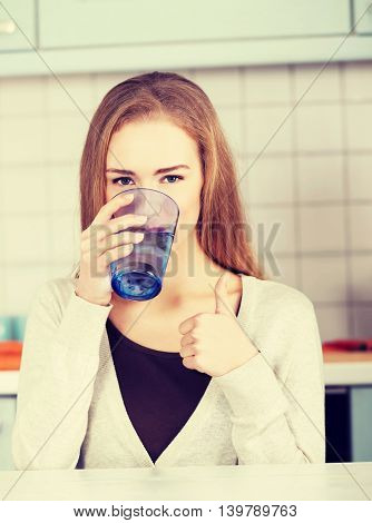 Beautiful caucasian woman sitting in the kitchen and drinking.