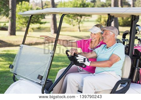 Smiling mature golfer woman showing to man sitting in golf buggy