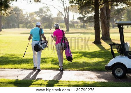 Rear view of mature golfer couple walking on field