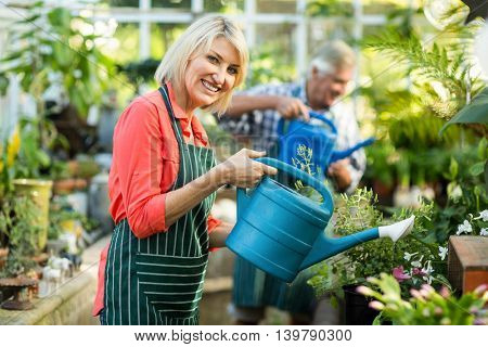 Portrait of happy woman watering plants with man at greenhouse