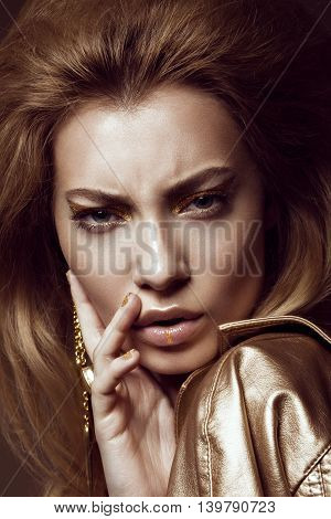Beautiful girl in a gold dress with creative makeup and hair. The beauty of the face. Photos shot in the studio.