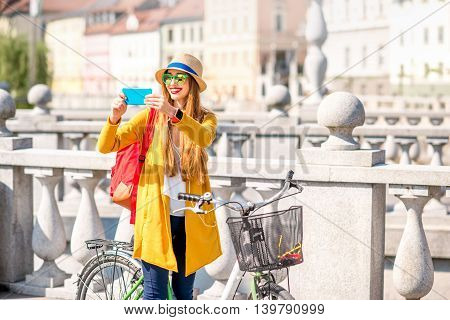 Young female traveler photographing city with smart phone standing with bicycle on Triple bridge in Ljubljana. Traveling in Slovenia
