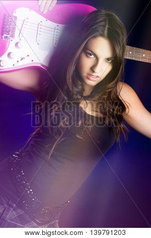 Beautiful rockstar girl holding electric guitar