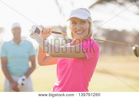 Confident mature woman carrying golf club by man standing on field