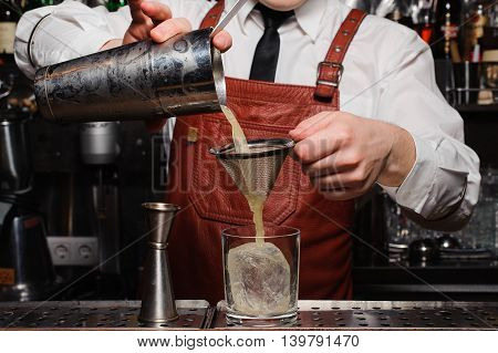 Bartender pouring fresh cocktail in fancy glass with ice