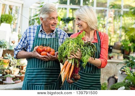 Gardeners smiling while holding fresh vegetables at greenhouse