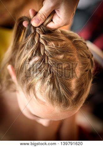 Mother Is Making Of Braids On Little Daughter's Head.