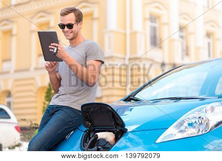 I am always in touch. Delighted young man with sunglasses reclining on his electric car and using a tablet while charging the car in the city