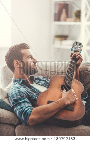 Composing new song. Thoughtful young man playing the guitar while lying on sofa
