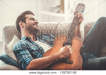 Music is his life. Happy young man playing the guitar while lying on sofa