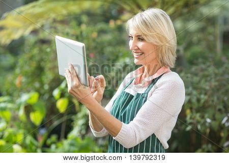 Happy mature female gardener using digital tablet at greenhouse