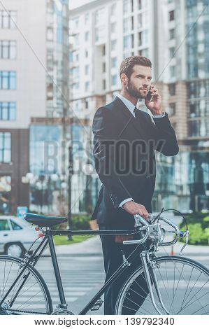 I will be in a time! Confident young businessman rolling his bicycle and talking on the mobile phone while walking outdoors