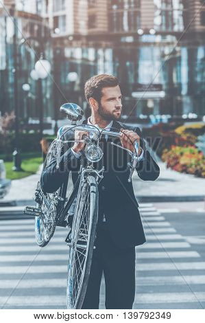 Green city transport. Confident young businessman carrying his bicycle on shoulder and looking away while crossing the street