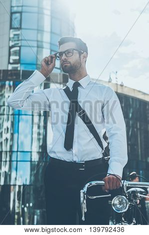 Confident businessman. Low angle view of confident young businessman adjusting eyewear and holding hand on his bicycle while standing outdoors