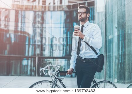 Enjoying fresh coffee. Thoughtful young businessman holding cup of coffee and looking away while leaning at his bicycle with office building in the background