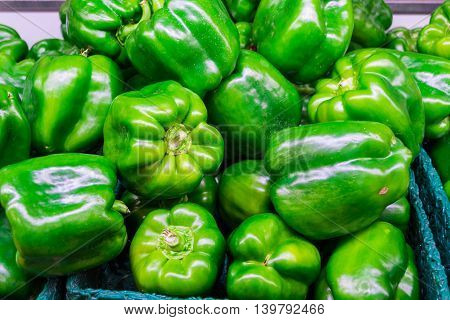 Many green peppers on shelf in store. Colorful food photography