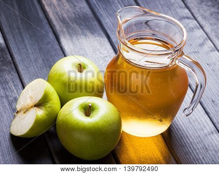 Apple juice in pitcher on table, photo still life