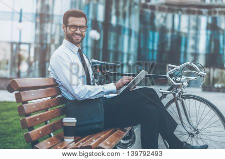 Confident and successful. Side view of smiling young businessman holding digital tablet and looking at camera while sitting on the bench near his bicycle
