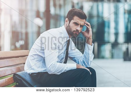 Feeling stressed after hard working day. Side view of depressed young businessman touching his forehead and looking away while sitting on the bench outdoors