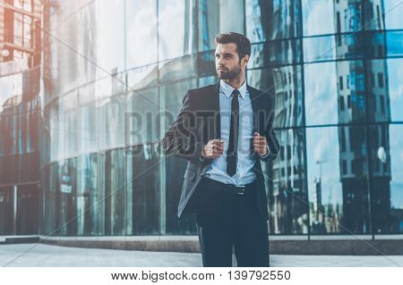 Young and successful. Handsome young businessman adjusting his jacket and looking away while walking outdoors with office building in the background