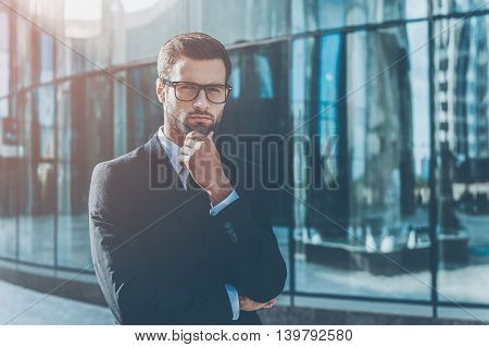 Business expert. Thoughtful young businessman holding hand on chin and looking at camera while standing outdoors with office building in the background