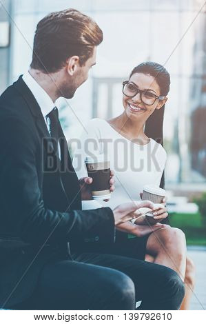 Enjoying coffee break. Two cheerful young business people holding cups of coffee and talking to each other while sitting outdoors