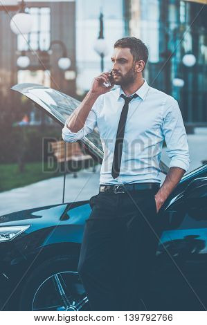 He needs a roadside assist. Confident young businessman talking on the mobile phone while leaning at the opened vehicle hood of his car