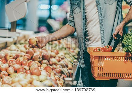 Choosing the freshest apples. Close-up of young man holding apple and shopping bag while standing in a food store
