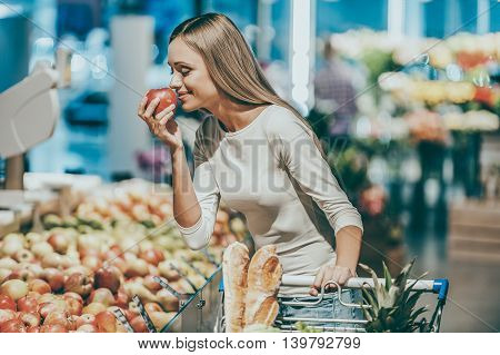 Choosing the freshest fruits. Beautiful young woman holding apple and smelling it with smile while standing in a food store