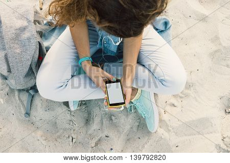 Young Slim Brunette Sits On The Beach In Jeans And Listening To Music With Headphones And Mobile Pho