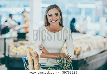 Woman in supermarket. Smiling young woman leaning at the shopping cart and looking at camera while standing in a food store
