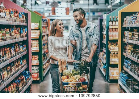 Shopping together is fun. Happy young couple bonding to each other and smiling while walking while walking in food store with shopping cart