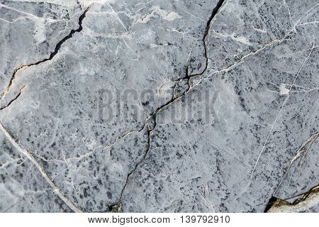 A cracked grey stone rock grunge texture