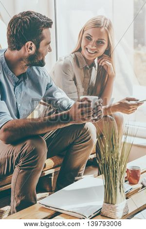 Coffee break. Smiling young woman holding mobile phone while young man holding cup of coffee and sitting near her in the rest area of the office