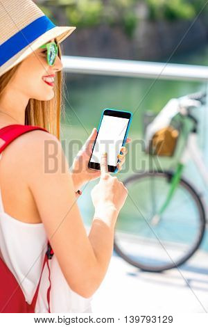 Female traveler holding smart phone with white screen on the street with bicycle on the background.