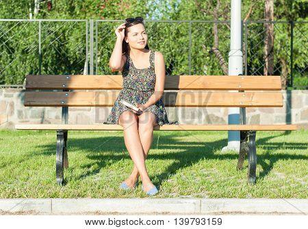 Girl Sitting On Bench Holding Sunglasses In Sunlight