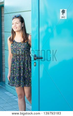 Girl Smiling And Using Public Restroom Outside