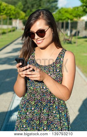 Girl Standing And Texting On Telephone Outside