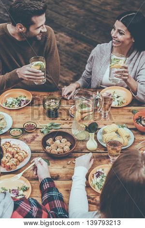 Dining with best friends. Top view of four people having dinner together while sitting at the rustic wooden table