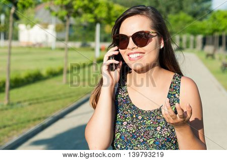 Woman Gesturing And Talking On Phone Outside
