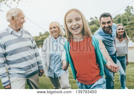 Family day. Happy little girl enjoying time with her family while walking outdoors together