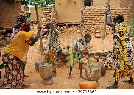 BANDIAGARA, MALI, AFRICA - AUGUST, 28, 2011 Dogon woman sings while other women grind millet