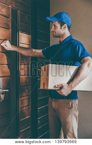 Delivery right to your door. Handsome young delivery man holding a cardboard box while knocking at the door of house