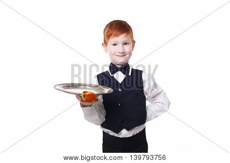 Little smiling waiter stands with empty tray serving something. Redhead child boy in suit plays restaurant servant isolated at white background