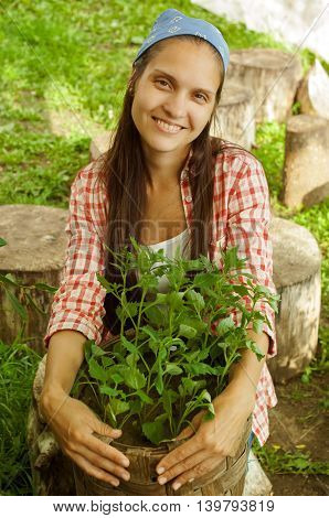 smiling girl in bandana holding a basket with seedlings