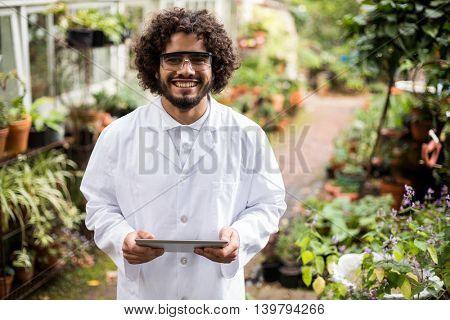 Portrait of confident male scientist holding digital tablet at greenhouse